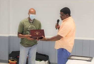 Jefferson County Sheriff Lafayette Woods, Jr., (right) presents custom gun box containing .40 cal  Glock service pistol to Major Randy Dolphin (left) at his retirement celebration.